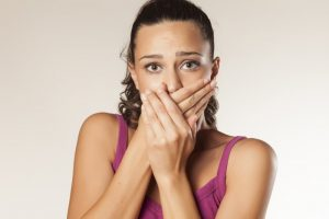 woman embarrassed covering her mouth