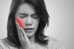 Woman holding mouth in pain
