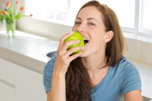 Woman in blue shirt eating apple