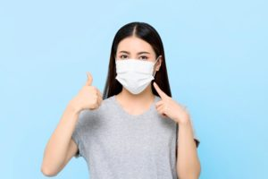 young woman wearing face mask and giving thumbs up to dentist in Las Cruces