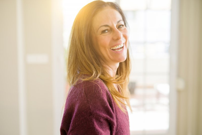 a middle-aged woman wearing a purple sweater and showing off her healthy smile
