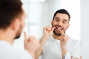 Man looking in the mirror flossing his teeth