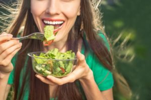 woman eating foods that benefit your oral health