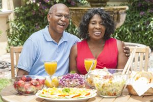 couple with dental implants in Las Cruces sitting at a table with various summer foods